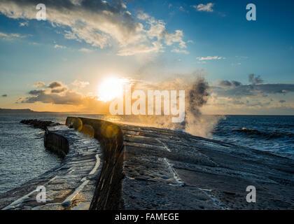 Lever du soleil sur la baie de Lyme Regis, comme une vague se brise contre la Cobb. Banque D'Images