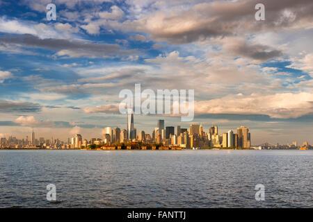 Gratte-ciel du quartier financier de Lower Manhattan, One World Trade Center et Ellis Island en fin d'après-midi, Banque D'Images