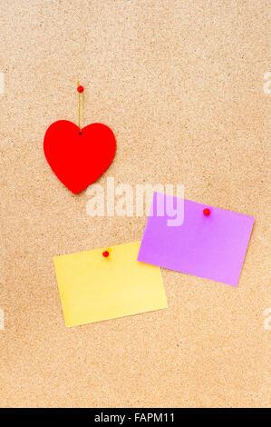 Saint Valentin coeur rouge et deux carte vide accroché à un panneau de liège à la verticale Banque D'Images