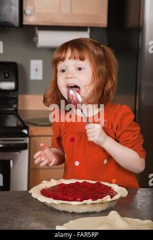 Quatre ans, fille de lécher un remplissage de cuillère cherry pie Banque D'Images