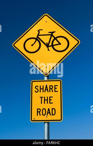 Partagez la route panneau de circulation contre un ciel bleu profond. Banque D'Images