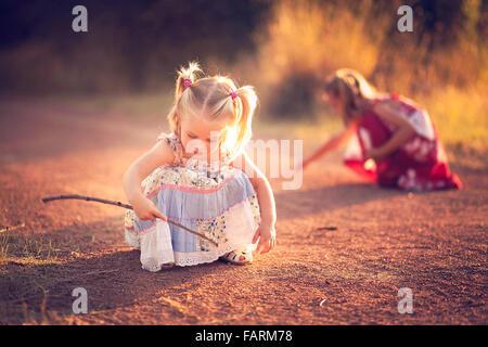 Petite fille jouant dans la saleté avec un stick Banque D'Images
