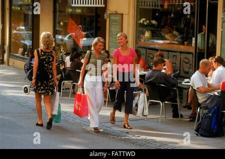 Trois femmes suédoises de trottoir en passant devant le restaurant de rue de Stockholm en été Banque D'Images
