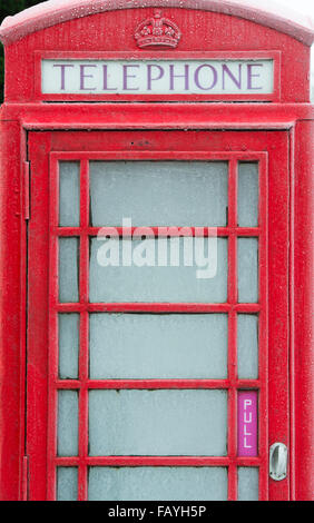 Vieux téléphone rouge fort couvert de givre. UK Banque D'Images