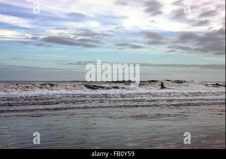 La silhouette du surfeur marche à travers le surf dans une mer d'hiver Banque D'Images