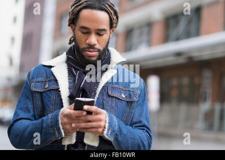 Homme sérieux avec des dreadlocks à l'aide de smart phone in street Banque D'Images
