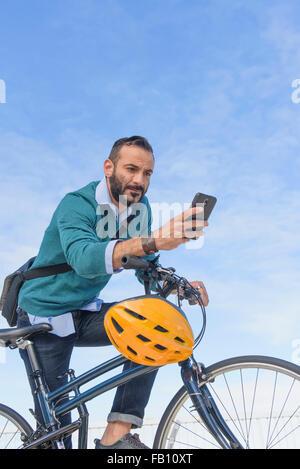 L'homme avec l'aide de vélo téléphone Banque D'Images
