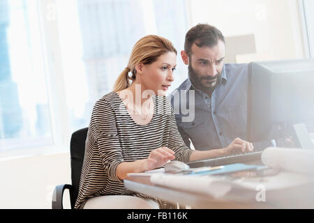 Man and Woman looking at computer in office Banque D'Images