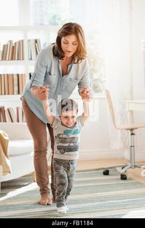 Mère tenant son (2-3) de faire les premières étapes Banque D'Images