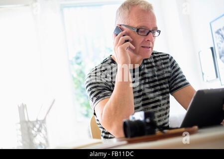 L'homme à l'aide de bureau à domicile tablette et smartphone Banque D'Images