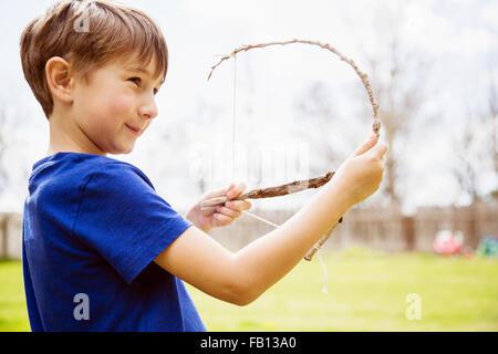 Portrait of boy (6-7) avec toy bow Banque D'Images