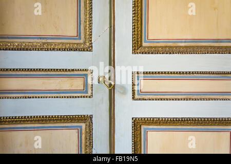 Une vieille porte peint décoré d'or, bleu et des lignes rouges Banque D'Images