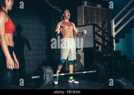 Pebbles homme tandis que dans d'entraînement d'haltères longues de sport Banque D'Images