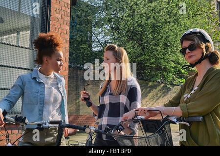 Les femmes en zone urbaine, jusqu'à la taille, debout tenant le chat bicyclettes Banque D'Images