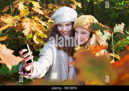 High angle view of teenage girls parmi les feuilles d'automne en utilisant smartphone pour prendre smiling selfies
