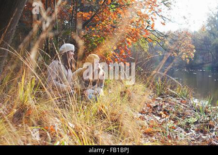 Adolescentes accroupi sur berge entre les hautes herbes à l'écart smiling