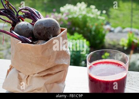 Sac de betterave bio et verre de jus de betteraves rouges sur la table de jardin Banque D'Images