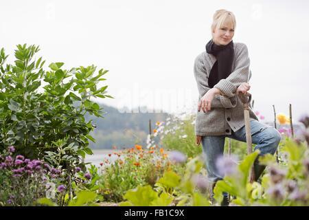 Portrait of mid adult woman creuser dans le jardin biologique Banque D'Images