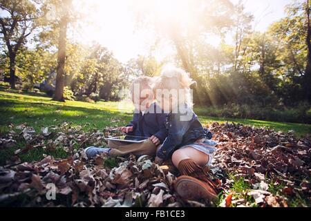Des enfants assis sur l'herbe couverte de feuilles d'automne à la recherche vers le bas à l'aide de tablette numérique Banque D'Images