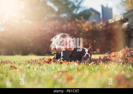Fille avec Boston terrier puppy couché à l'avant sur l'herbe couverte de feuilles d'automne, reposant sur le coude Banque D'Images