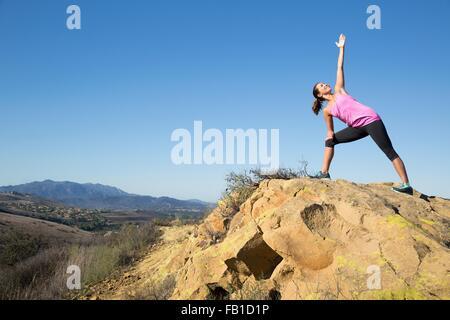 Woman practicing yoga posent sur hill, Thousand Oaks, Californie, USA Banque D'Images