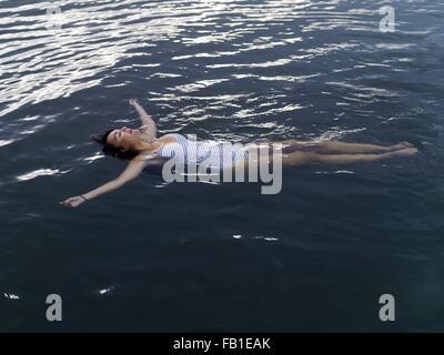 Portrait de femme flottant sur le dos dans l'eau les bras tendus jusqu'à Banque D'Images