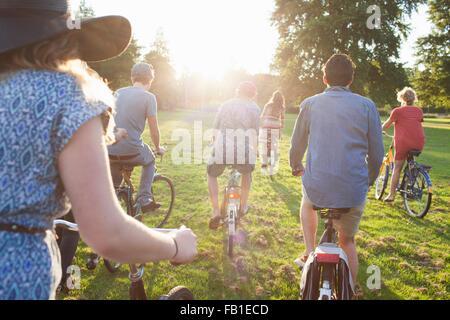 Vue arrière du parti va adultes arrivant au parc à vélos au coucher du soleil Banque D'Images