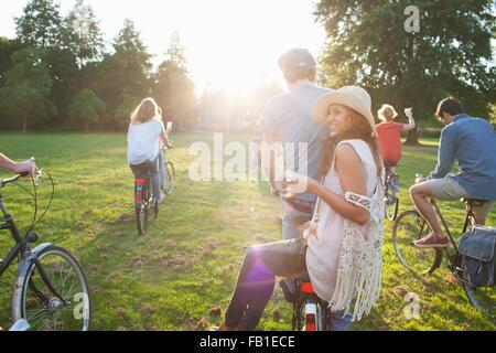 Vue arrière du parti va adultes dans le parc à vélo au coucher du soleil Banque D'Images
