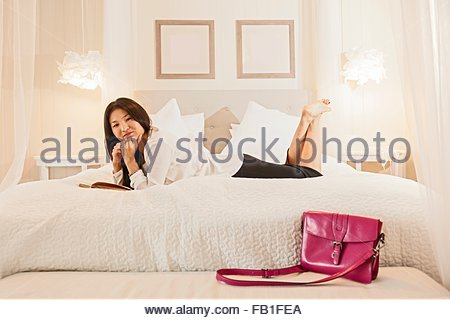 Business Woman relaxing on bed in hotel room Banque D'Images