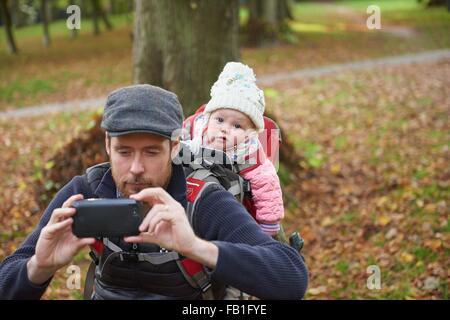 Parc de télévision portant sur l'exécution de la fille en prenant l'aide de porte-bébé selfies smartphone Banque D'Images