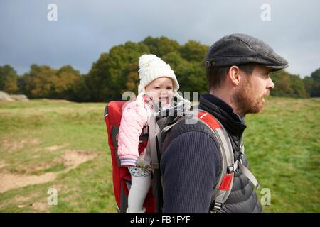 Vue latérale du champ de man wearing flat cap portant sur fille en porte-bébé Banque D'Images