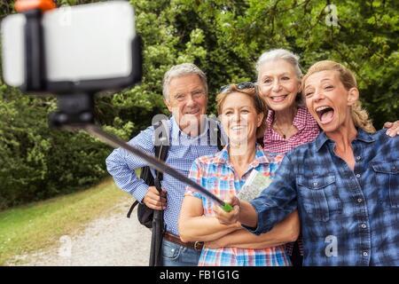 Groupe d'amis taking self portrait, à l'aide de bâton selfies et smartphone Banque D'Images