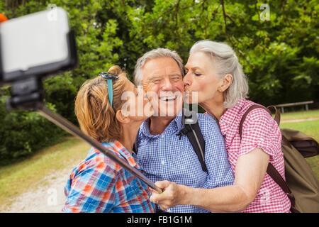Groupe d'amis taking self portrait, à l'aide de bâton selfies et smartphone, women kissing man on cheek Banque D'Images