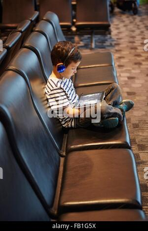 Jeune garçon assis dans la salle d'attente de l'aéroport, using digital tablet Banque D'Images