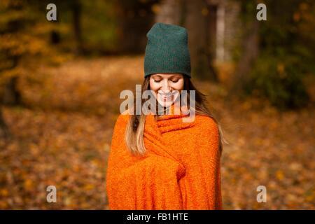 Jeune femme enveloppée dans une couverture orange en forêt d'automne Banque D'Images