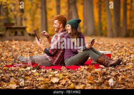 Couple using digital tablet et smartphone en forêt Banque D'Images