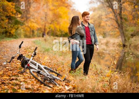 Jeune couple romantique sur riverside en automne Banque D'Images