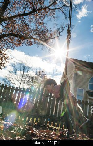 Vue de côté de l'angle faible Garçon jouant sur la balançoire dans le jardin