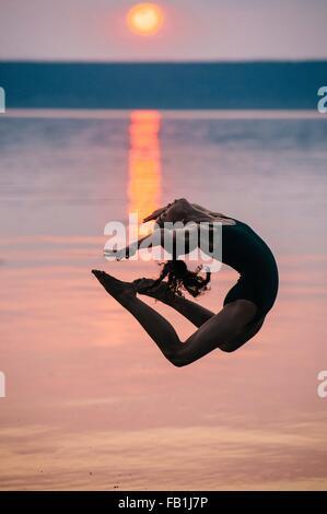 Vue de côté de l'océan au coucher du soleil par fille, sautant en l'air vers l'arrière de flexion Banque D'Images