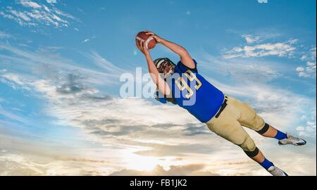 Les adolescents de sexe masculin American football player catching ball mid air against blue sky Banque D'Images