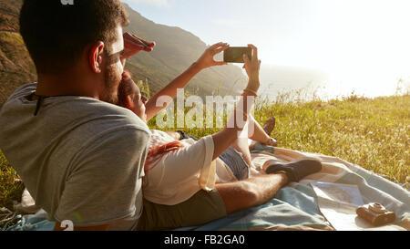 Vue arrière du jeune couple sur un autoportrait en pique-nique avec leur téléphone intelligent. Banque D'Images