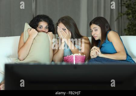 Pour regarder un film de terreur à la télévision assis sur un canapé à la maison Banque D'Images