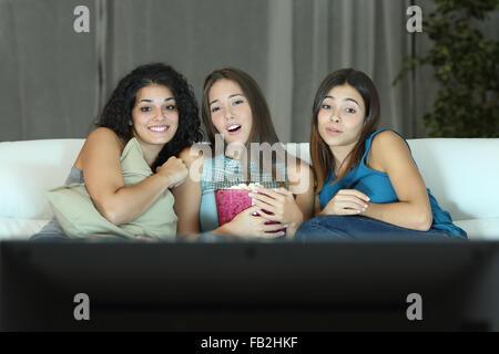 Trois amis regarder film romantique sur la tv assis sur un canapé à la maison Banque D'Images