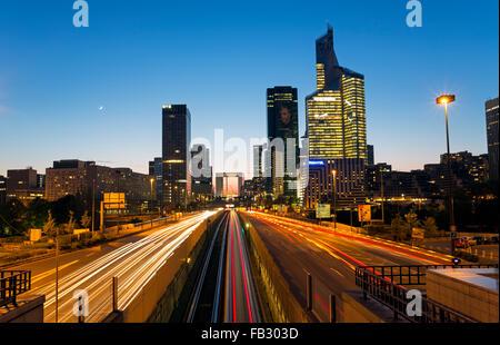 Route de Paris la nuit menant vers la Grande Arche et immeubles de bureaux modernes à la Defense, Paris, France