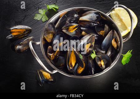 Les moules cuites dans un plat de cuisson sur un fond sombre. Vue d'en haut
