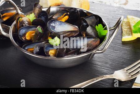 Les moules cuites dans un plat de cuisson sur un fond sombre. Selective focus