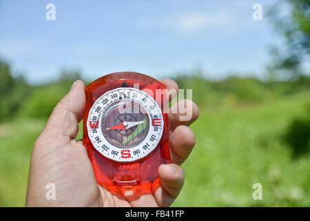 Man's hand holding compass au contraire recentrer paysage estival. Banque D'Images