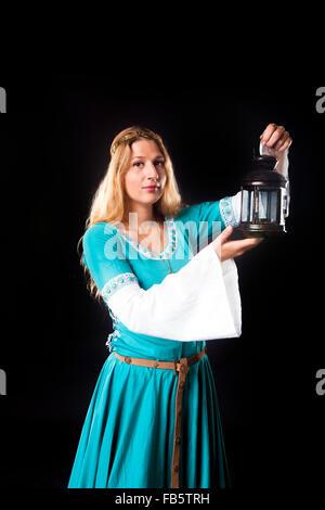 Portrait de jeune fille dans une robe turquoise médiévale regardant la caméra tout en maintenant une lampe de style Banque D'Images