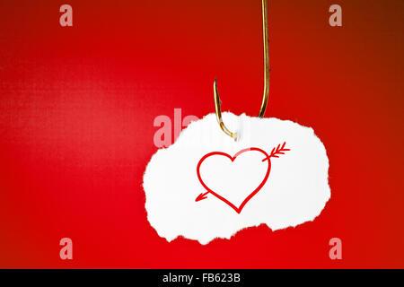 Un coeur transpercé d'une flèche tracée sur la feuille de papier blanc suspendu à un crochet de pêche sur fond rouge. Banque D'Images
