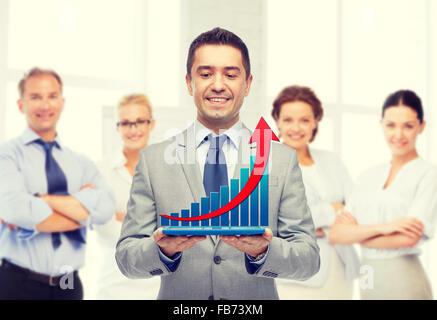 Happy businessman in suit holding tablet pc Banque D'Images